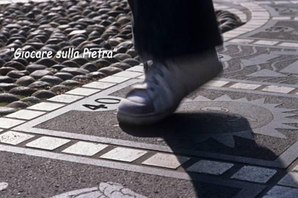 Foto che mostra un particolare di una persona che sta giocando su un pavimento di pietra.