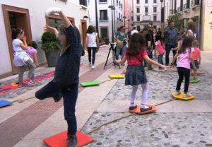 Bambine che giocano in una via cittadina.